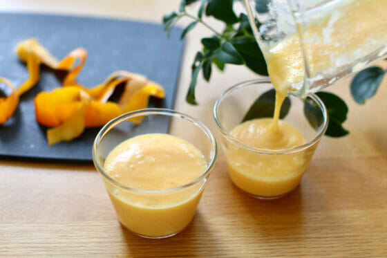 ジュース状にした柿をカップに注ぐ
