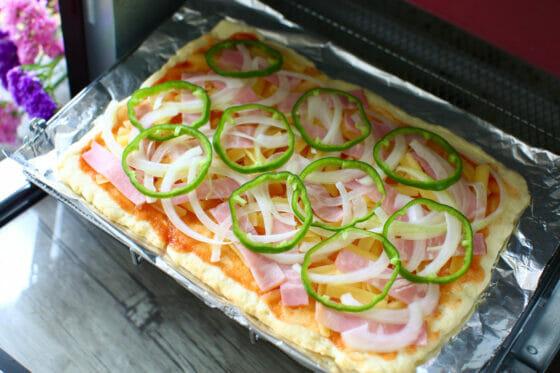 ホットケーキミックスのピザ生地にチーズとベーコンと玉ねぎとピーマンをのせる