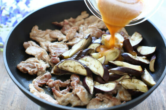 豚肉に茄子と調味料を加える