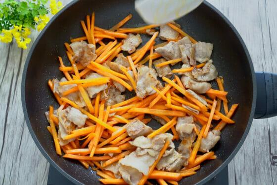フライパンで人参と豚肉を炒める